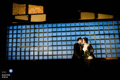 Chicago wedding photographer captured this image of a bride and groom kissing in front of a window