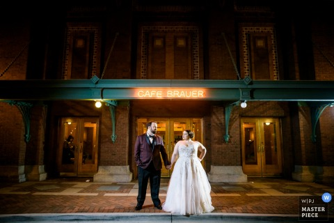Chicago wedding photographer created this portrait of a bride and groom holding hands outside a cafe at night