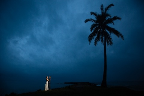 Wedding Photographer David Clumpner of Montana, United States - Well-lit portrait, and including the palm tree was a brilliant idea. The time of night was perfect to include the drama of the clouds.
