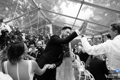 This black and white image of a groom happily high-fiving a wedding guest under a glass ceiling was captured by a New South Wales wedding photographer
