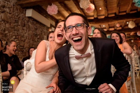 This portrait of a bride and groom laughing at something off camera was captured by a Nantes wedding photographer