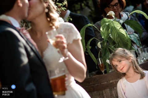 Nantes wedding photographer captured this image of a bride and groom kissing in the sunshine while the flower girl watches adoringly
