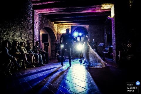 Fotograf ślubny w Mediolanie uchwycił ten obraz młodej pary tańczącej na ciemnym parkiecie z niebieskimi i fioletowymi światłami za nimi