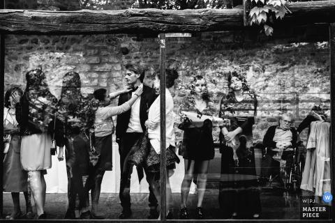 Genua-Hochzeitsfotograf nahm dieses Schwarzweiss-Porträt der Hochzeitsgäste gefangen, die heraus das Fenster beim Warten auf die Braut und den Bräutigam schauen