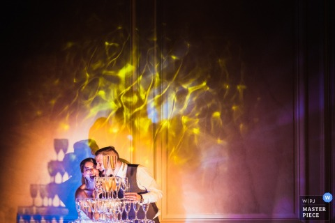 France wedding photographer created this image of the bride and groom laughing behind a champagne glass tower.