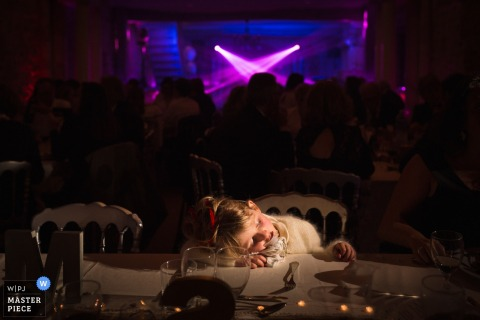France wedding photographer captured this wedding guest sleeping on the table at an indoor wedding reception.