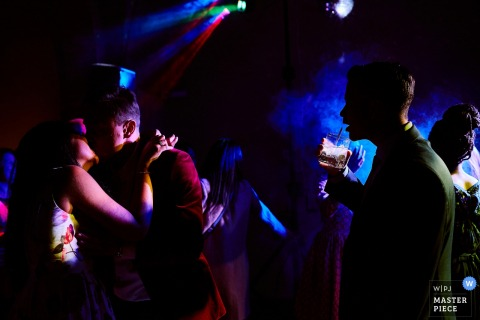 Florence wedding photographer created this image of a bride and groom kissing on a darkly lit dance floor while guests watch