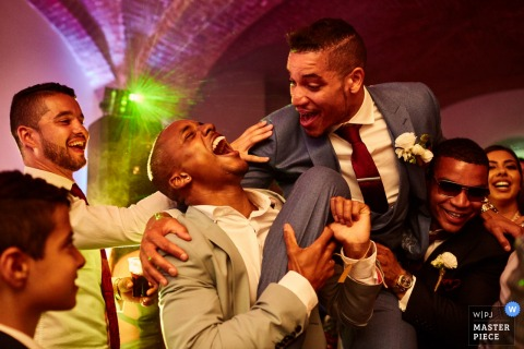 Florence wedding photographer captured this humorous picture of a groom being held by his groomsmen and laughing