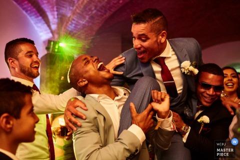 El fotógrafo de bodas de Florence capturó esta imagen humorística de un novio en manos de sus padrinos de boda y riendo