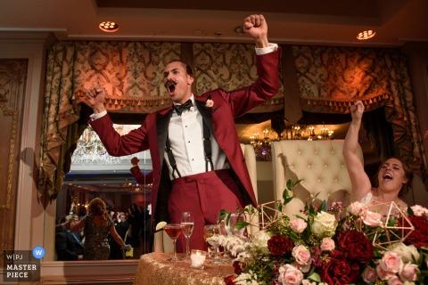 New York City-Hochzeitsfotograf schuf dieses humorvolle Bild eines Bräutigams, der an seinem Empfang in einem roten Anzug feiert
