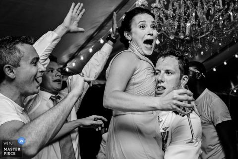 Key West-huwelijksfotograaf heeft dit beeld van de bruidspartij gemaakt en dwaas en plezier gemaakt met hun drankjes op de receptie-dansvloer.