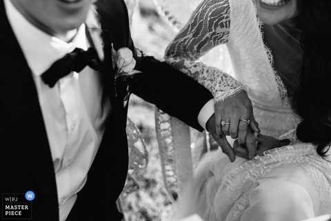 New South Wales wedding photographer captured this detail shot of a bride and groom holding hands in their wedding dress and tuxedo
