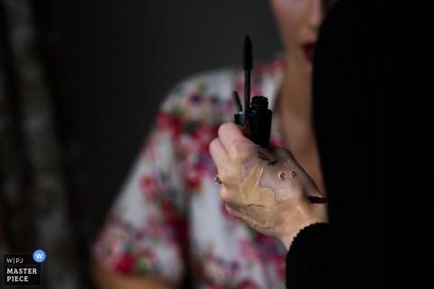 Nottinghamshire-Hochzeitsfotograf nahm dieses Detailbild der befleckten Hand des Cosmetologistsmake-up auf, die einen Wimperntuschenstab hält, während die Braut in der Nähe sitzt
