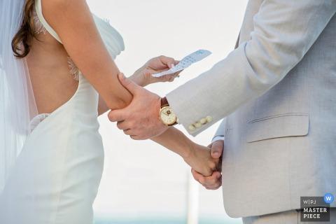 Key West-huwelijksfotograaf ving deze foto van een bruid en bruidegomholdingshanden terwijl het ruilen van hun geloften bij hun openluchtceremonie op een zonnige dag
