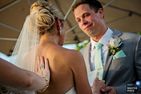 De huwelijksfotograaf van Key West creëerde deze foto van een bruid en een bruidegom die geloften bij hun openluchtceremonie op een zonnige dag ruilen
