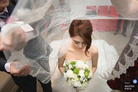 Taipeh-Hochzeitsfotograf nahm dieses Bild von oben genanntem der Hochzeitsgäste gefangen, die einen Brautschleier hochhalten, während sie an zu ihrem Blumenstrauß der weißen Rose hält