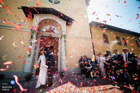 Brescia wedding photographer captured this image of a bride and groom being showered with brightly colored confetti while standing in the sunshine outside of a church