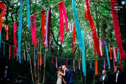 London wedding photographer captured this image of colorful banners strung from tree to tree in a forest while the bride and groom kiss in the background