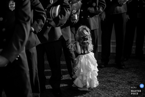 New Jersey wedding photographer captured this black and white image of a little girl in a white dress gazing up at the police officers that surround her