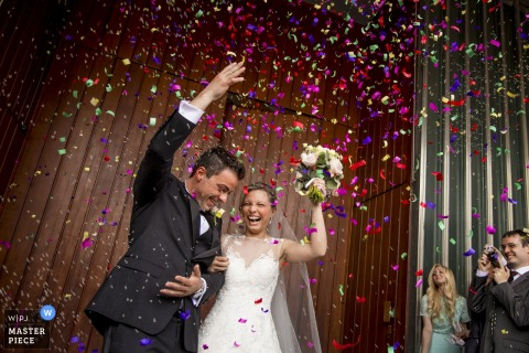 Lecco wedding photographer captured this image of a bride and groom standing under a shower of pink and purple confetti