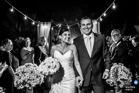 Brazil wedding photographer captured this black and white photo of a bride and groom holding hands under a night sky while wedding guests watched adoringly