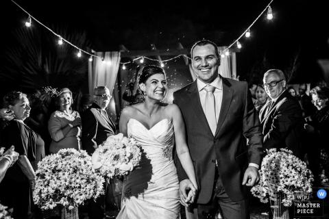 El fotógrafo de bodas de Brasil capturó esta foto en blanco y negro de una novia y un novio tomados de la mano bajo un cielo nocturno mientras los invitados de la boda observaban con adoración