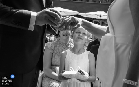 Holland wedding photographer created this black and white photo of a ring bearer watching the bride and groom exchange rings at an outdoor ceremony