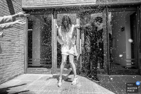 Argentina wedding photographer captured this black and white picture of a bride and groom being showered with confetti outdoors
