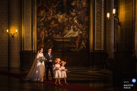 De huwelijksfotograaf van Frankrijk ving deze foto van een bruid en een bruidegom die achter twee bloemmeisjes lopen voor een groot schilderij
