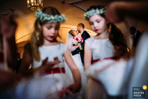 Germany wedding photographer captured this image of a bride and groom kissing behind the flowergirls