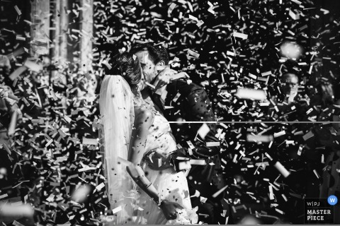 Madrid wedding photographer captured this image of a bride and groom kissing surrounded by confetti