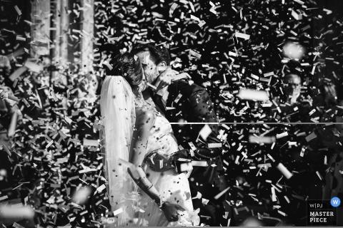 El fotógrafo de bodas de Madrid capturó esta imagen de una novia y un novio besándose rodeado de confeti.