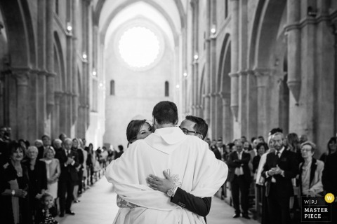 Lazio wedding photographer created this black and white image of a bride and groom hugging the priest in a church