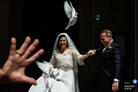 Rome wedding photographer captured this image of a happy bride and groom leaving the ceremony while a dove was released