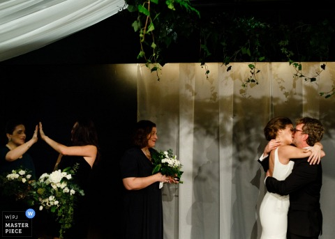 El fotógrafo de bodas de Toronto capturó esta imagen de un puente y un novio besándose en su ceremonia de boda al aire libre mientras los miembros de la fiesta nupcial celebran.