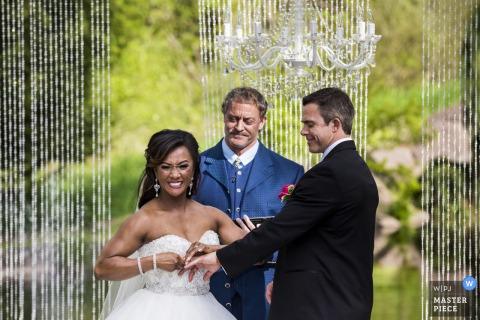 El fotógrafo de bodas de Tacoma capturó esta imagen de una novia que colocaba el anillo de bodas en el novio en su ceremonia al aire libre