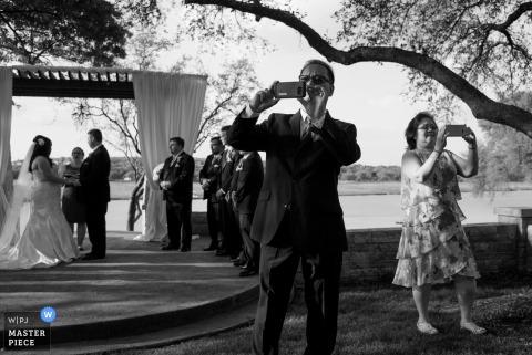 El fotógrafo de bodas de Austin hizo esta imagen en blanco y negro de los invitados que tomaban fotos durante una ceremonia de oudoor bajo árboles de sombra.