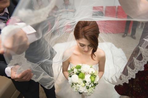 La novia se lleva el velo sobre la cabeza durante una ceremonia de boda china. Foto de boda por Chiang Yuan Hung de Taiwan