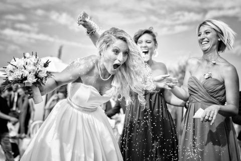 Una novia en Arezzo, Italia recibe un poco de confeti vertido sobre ella por una dama de honor en su boda. Foto de Fabio Mirulla.