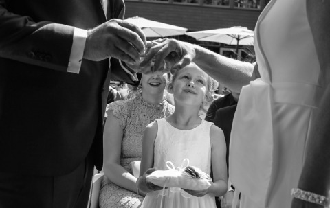 A Documentary Wedding Photographer in Noord Holland, Netherlands, Peter Kos created this lovely black and white photo of a flowergirl looking at the bride and groom during the outdoor vow exchange.