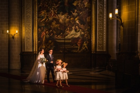 El fotógrafo de bodas de Francia, Ronan Jégaden, hizo esta hermosa foto con mucha luz dentro de la iglesia de una novia que caminaba a su ceremonia con papá y dos floristas.