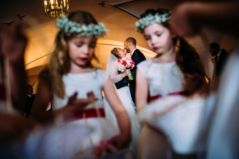Germany Wedding Photographer Andreas Pollok made this image through the flowergirls of the bride and groom kissing after the indoor ceremony.