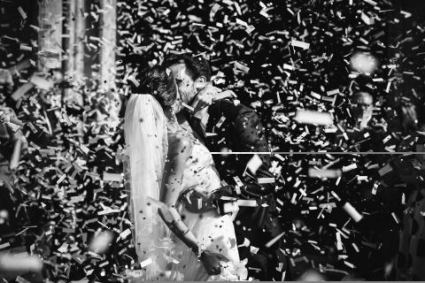 Una gran fiesta de confeti esperó a estos novios después de la ceremonia de boda de su iglesia en Madrid, España. Fotografía de boda en blanco y negro de Alicia Gonzalez-Haro.
