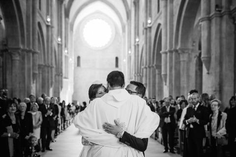 La novia y el novio abrazan al sacerdote dentro de la iglesia después de su ceremonia de boda. Foto de boda de Nando Ginnetti de Latina, Italia.
