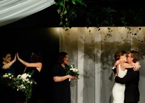 Ontario, Canadá El fotógrafo de bodas Ben Benvie hace fotos de la ceremonia como esta: una de las novias besándose mientras las damas de honor celebran.