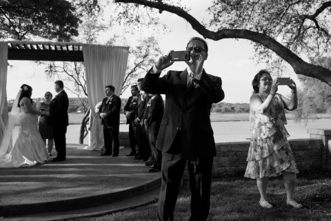 Photographer Brett Buchanan captured the wedding guests using their own cameras during the outdoor ceremony in Texas.
