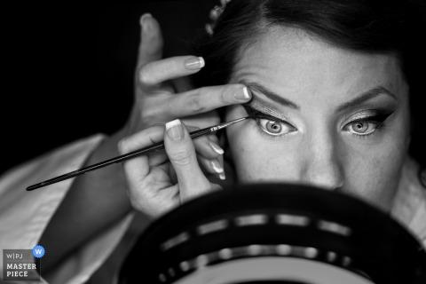 Tuscany wedding photographer created this closeup image of a bride carefully applying eyeliner with a brush