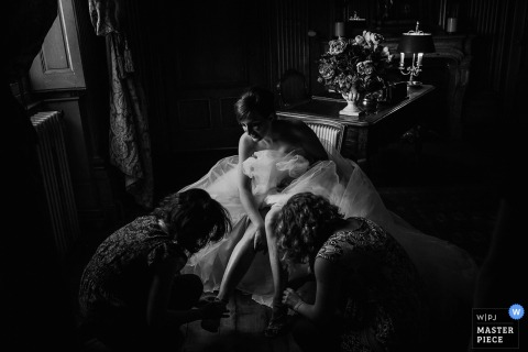This black and white photograph of a bride getting assistance putting on her shoes while in her wedding gown was captured by a Lyon wedding photographer