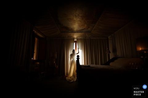 Fotograf ślubny Umbria uchwycił to zdjęcie sylwetki panny młodej stojącej przed jasnym oknem w ciemnym pokoju