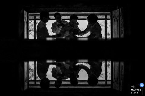 Fuzhou wedding photographer captured this black and white image and reflection of the groomsmen assisting the groom in getting ready for the wedding ceremony